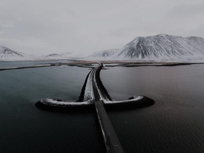 Eine Brücke, die über einen See auf ein Bergpanorama zuführt.