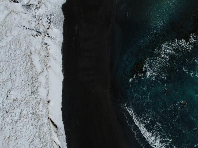 Landschaft mit Schnee, schwarzem Sand und Meer.