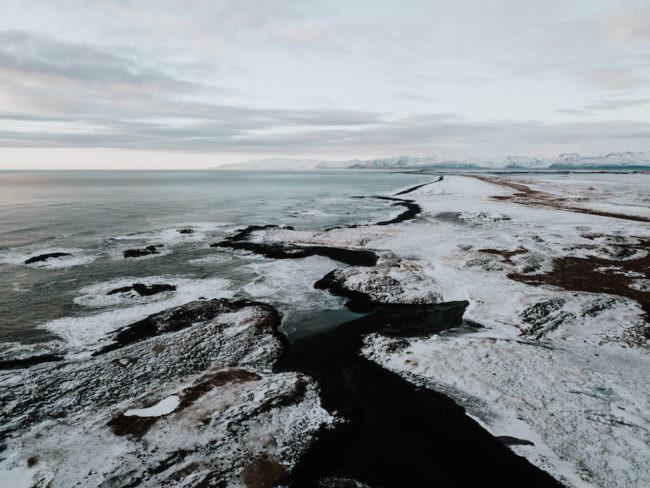 Verschneite Küstenlinie mit schwarzem Sand.
