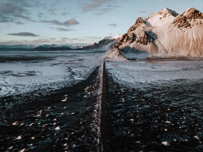 Eine schwarze Straße, die zu einem Bergpanorama führt.