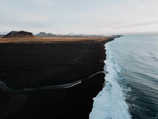 Eine Küstenlinie mit schwarzem Sand.