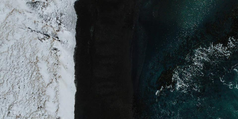 Draufsicht auf eine Landschaft mit Schnee, schwarzem Sand und Meer.