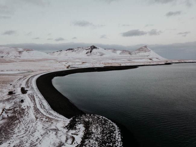Ein Strand mit schwarzem Sand am Meer vor einer verschneiten Landschaft.