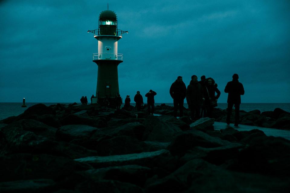 Ein Leuchtturm am Meer mit vielen Menschen, die auf einem Weg davor laufen