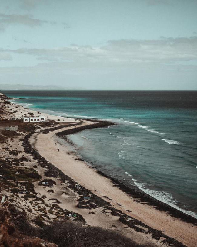 Eine Küstenaufnahme mit einem Strand und dem Meer.