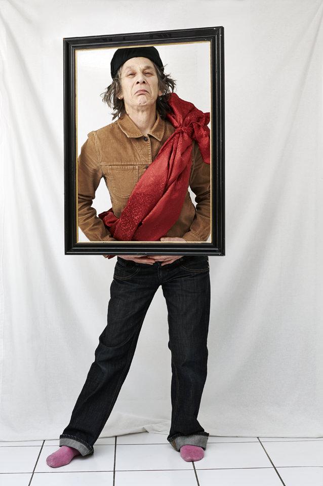 Person vor Studiohintergrund posiert vor einem Bilderrahmen. Dabei hat sie eine rote Scherpe um.