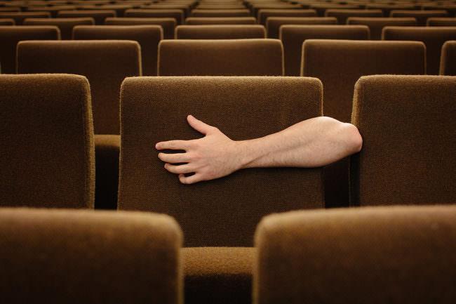 Ein Arm umarmt einen Sitz im Kino