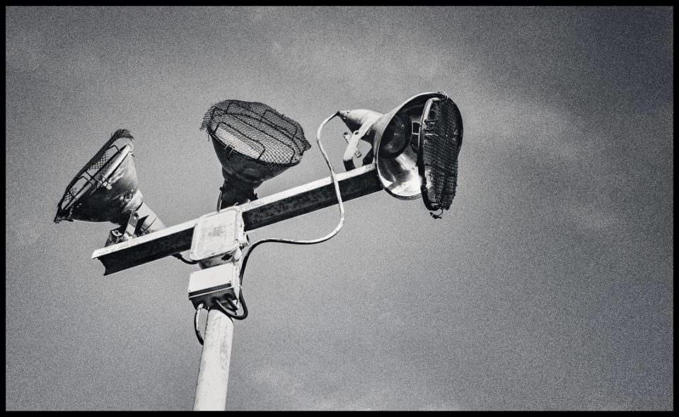 Schwarzweißansicht eines großen Außenstrahlers mit 3 großen Lampen, davon ist einer beschädigt, vor Himmelgrund.