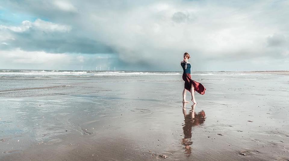 Eine Frau mit wehendem Rock steht an einem Strand am Meer.