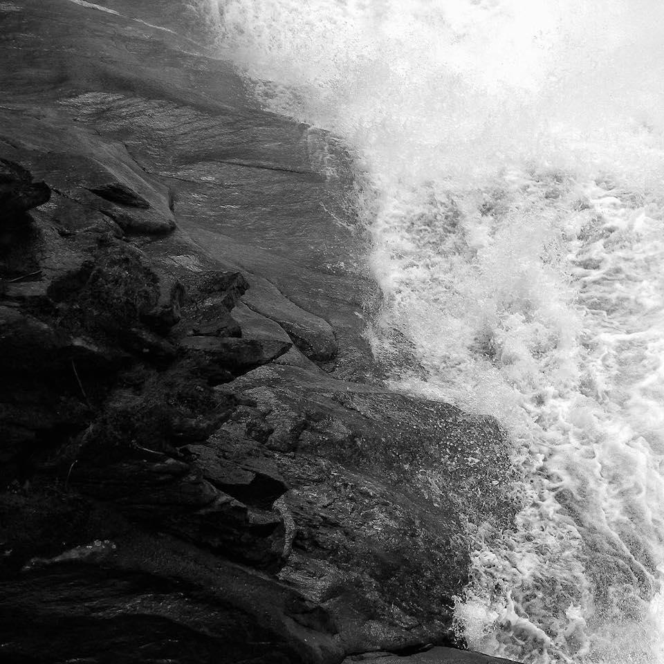 Wellen, die auf Felsen treffen