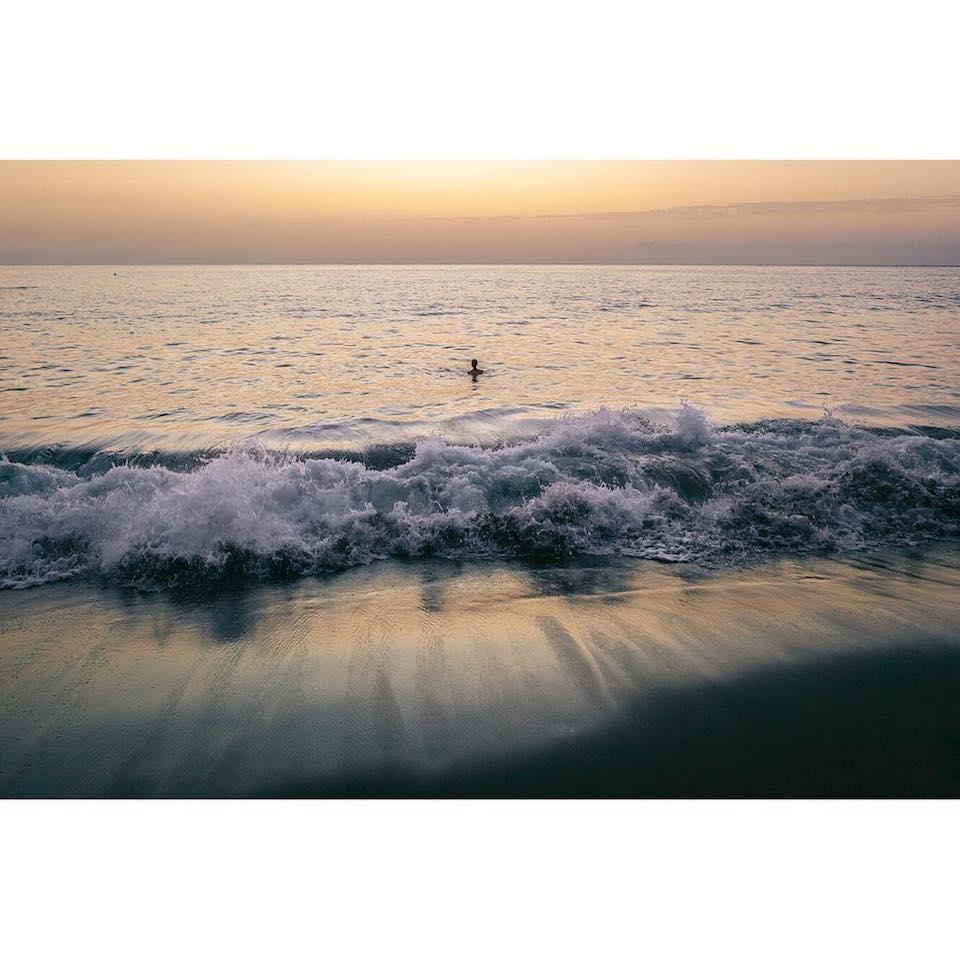 Ein einzelner Mensch, der im Meer schwimmt, vom Strand aus