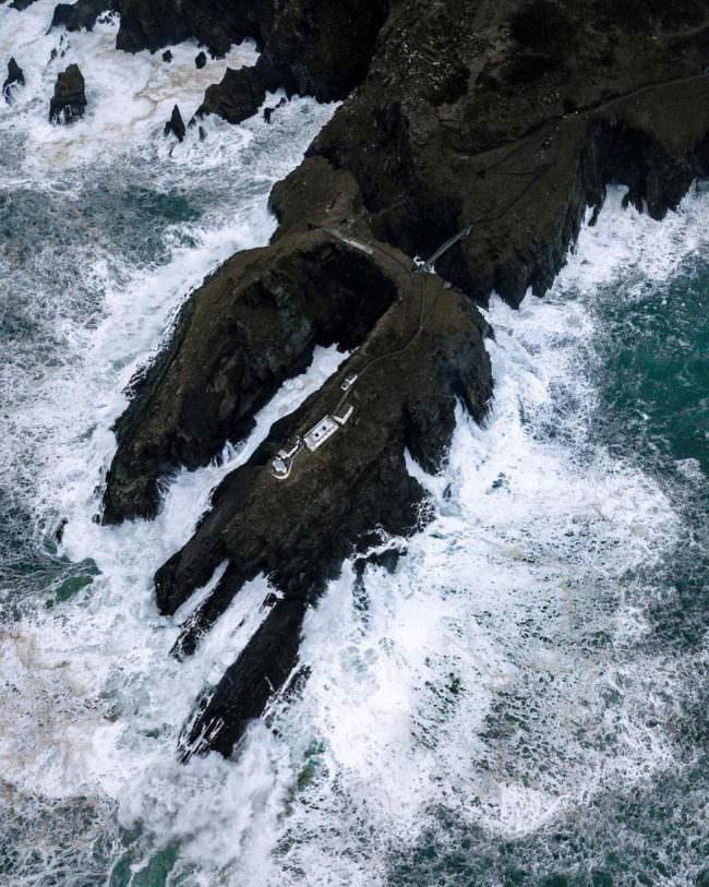 Drohnenfoto einer Bucht am Meer mit reißenden Wellen