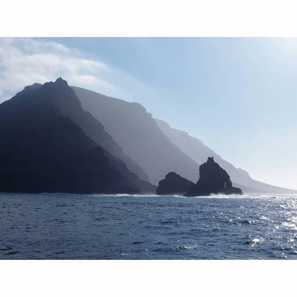 Felsen im Meer, über die die Sonnenstrahlen scheinen.