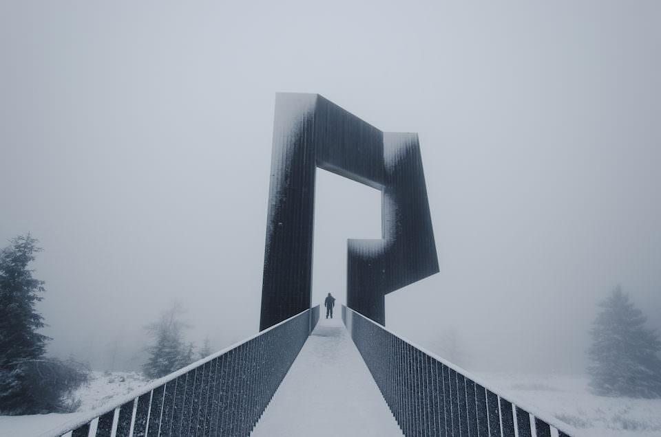 Eine Person unter einem schneebedeckten Monument