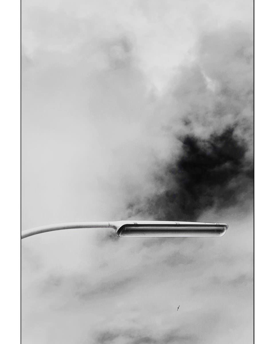 Eine einsame, längliche Straßenlaterne in schwarzweiß vor einem Wolkenloch.