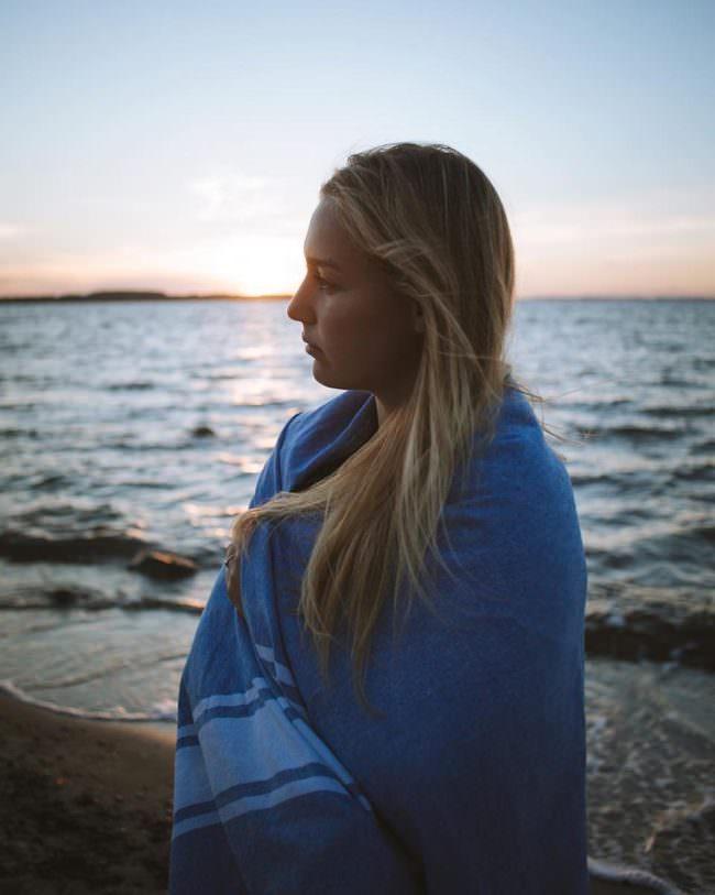 Eine Frau wärmt sich mit einer Decke am Meer bei Sonnenuntergang.