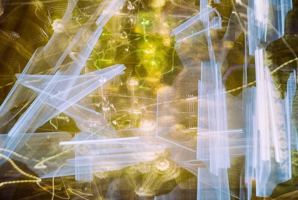 Abstraktes Lichtspiel in Gelb und Blau mit verwirrenden, feinen Linien.