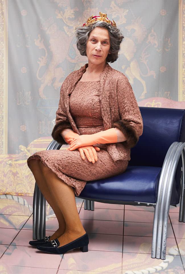 Frau in Kostüm der Queen sitzt andächtig auf einem blauen Stuhl.