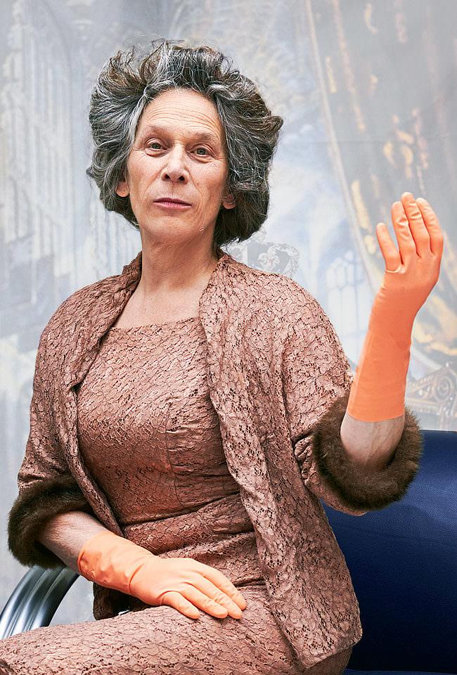 Frau in Kostüm der Queen sitzt andächtig auf einem blauen Stuhl und macht die königliche Handgeste.