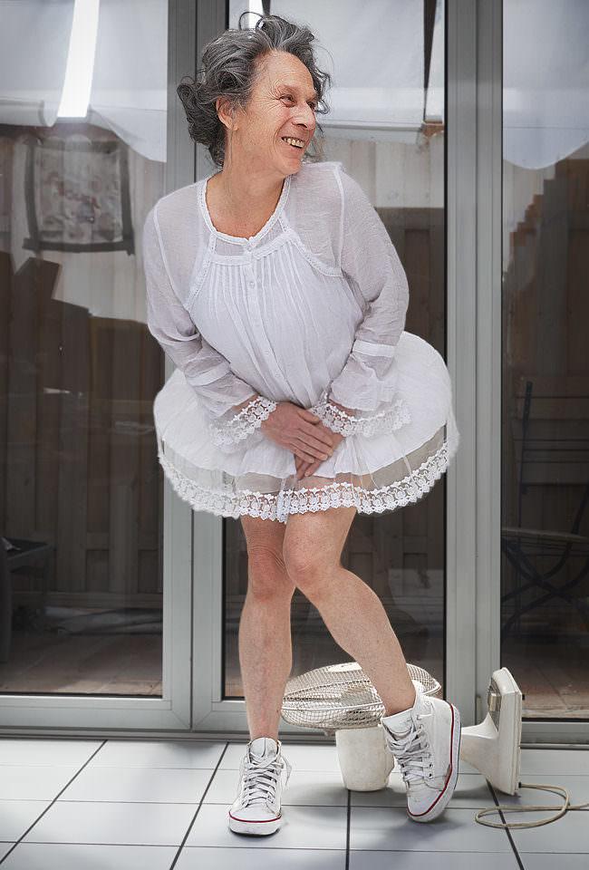 Frau in weißem Kleidchen, das von einem Ventilator hochgeweht wird.