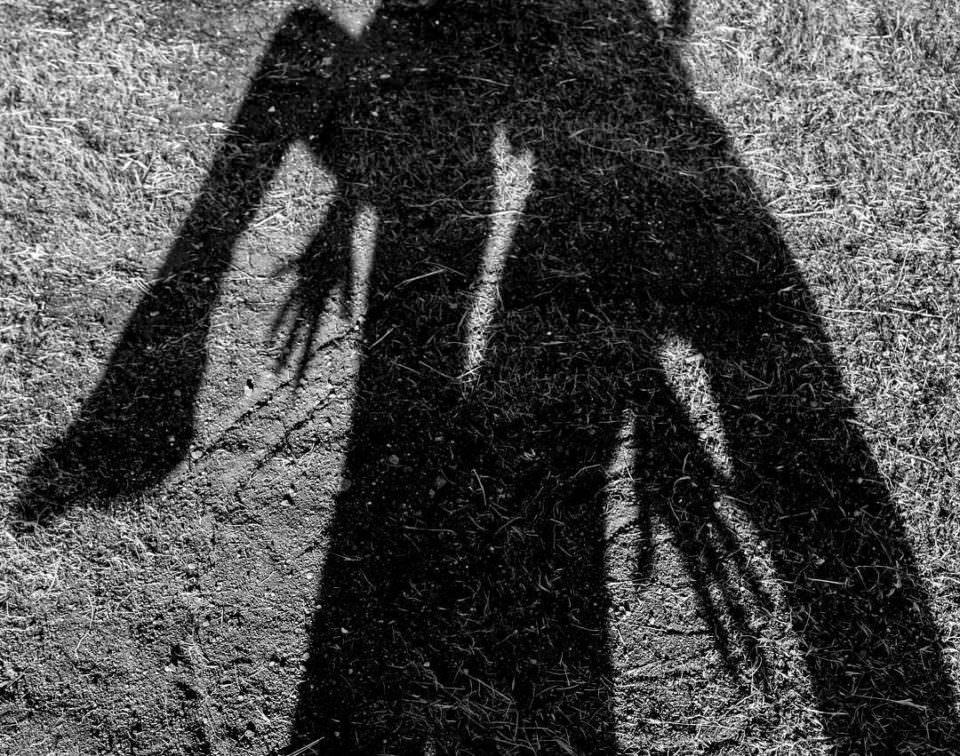 Schwarzweißer Schattenwurf auf trockenen, sonnenbeschienenem Grasgrund mit erkennbaren Gliedmaßen zweier Personen.