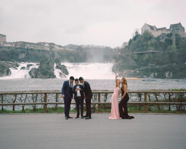 Eine Gruppe Menschen fotografiert sich selbst vor einer Landschaft