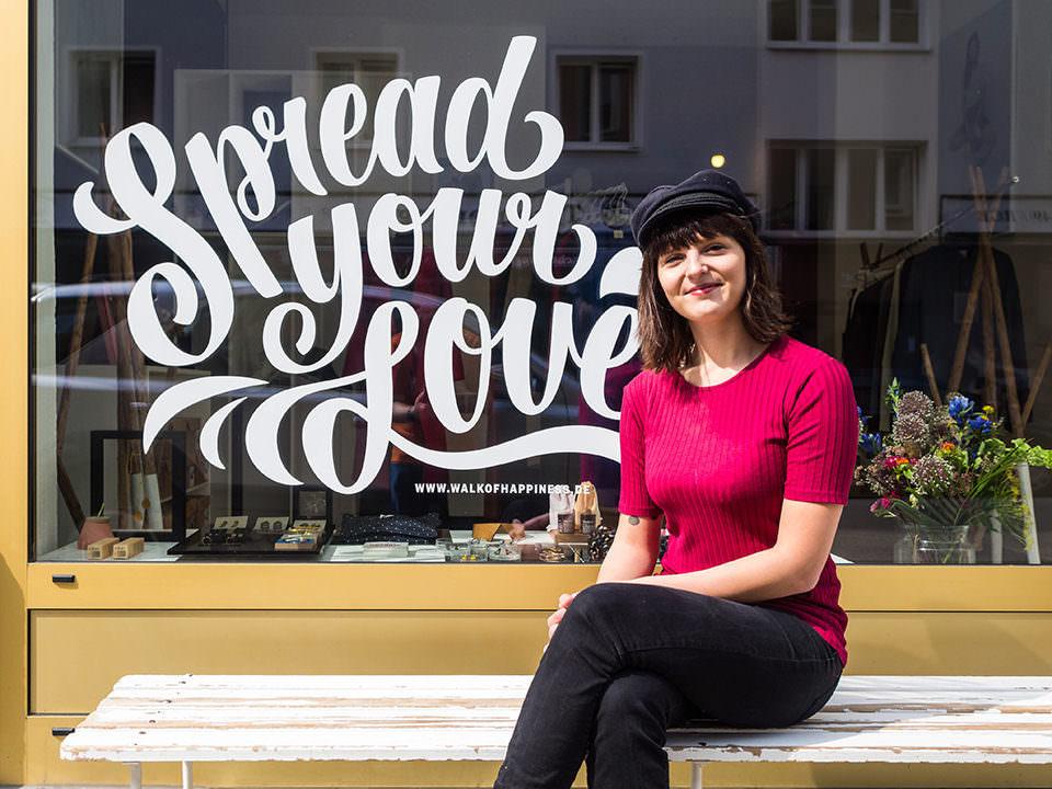 """Junge Frau mit dunklen Haaren und einer Mütze auf sitzt vor einem Schaufenster auf dem in geschwungenen Buchstaben """"Spread your Love"""" steht."""