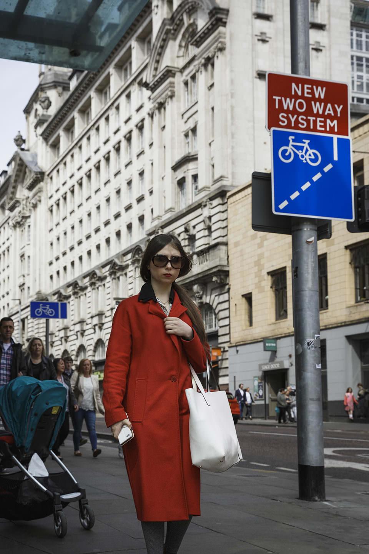 """Frau in rotem Mantel mit Sonnenbrille auf einer städtischen Straße. Am Arm einen weißen Beutel. Neben ihr ein Schild, auf dem Steht: """"New two way System"""""""