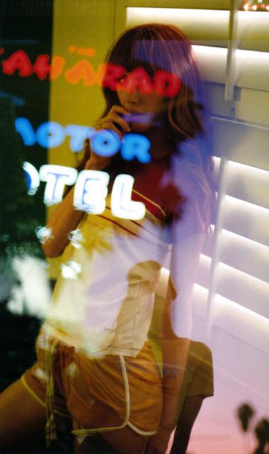 Frau mit Spiegelung eines Werbeschildes
