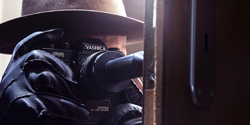 Spionagefotograf mit Hut und Lederhandschuhen fotografiert mit besonderer Kamera durch etwas hindurch.