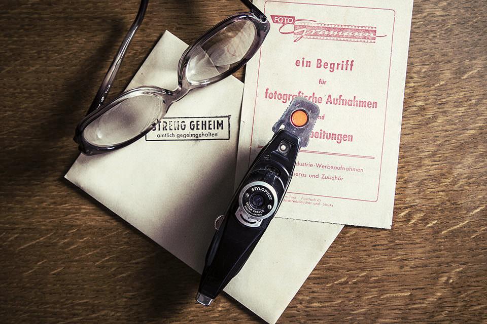 Auf einer Holzpberfläche liegen geheime Briefsachsen, eine Brille und ein sonderbares Kameragerät.