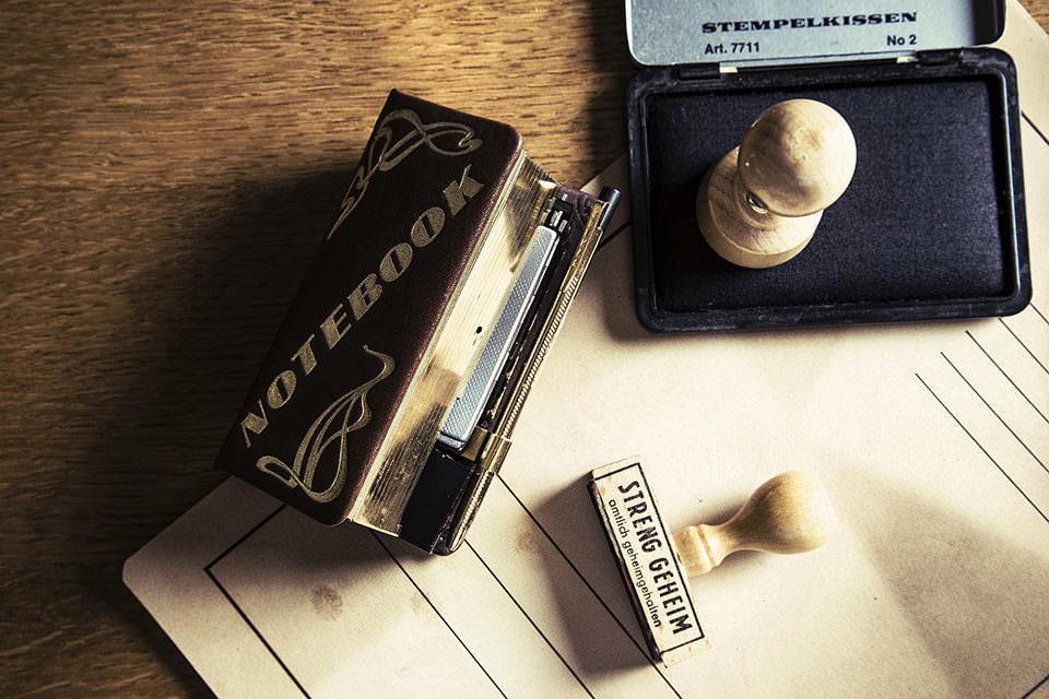 Aktenmappe, Notizbuch und Stempelkissen mit Stempeln auf einem Tisch.