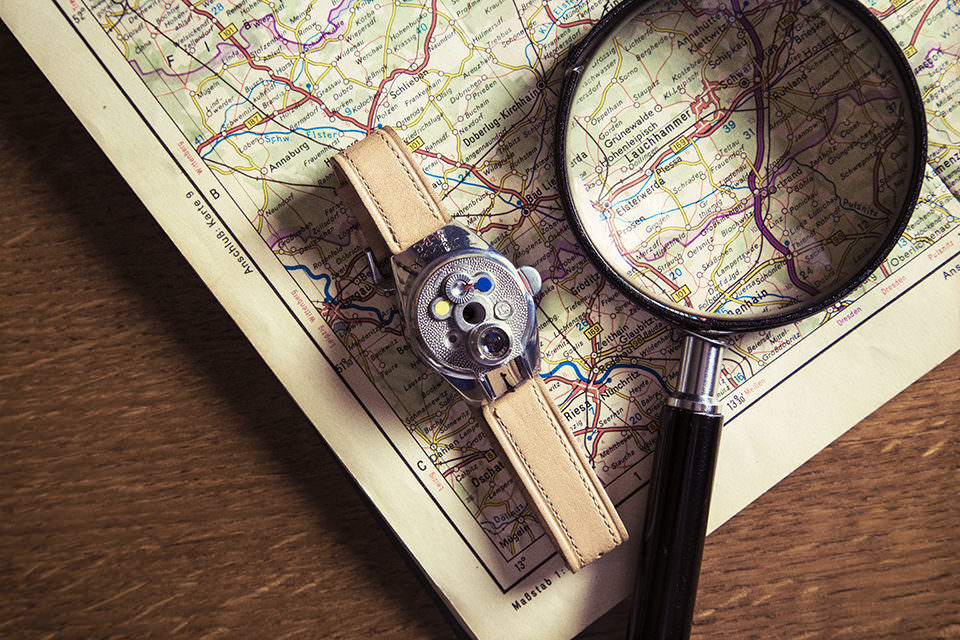 Auf einem Holzuntergrund liegt eine Landkarte, auf der eine Lupe liegt. Daneben befindet sich eine Kameraarmbanduhr.