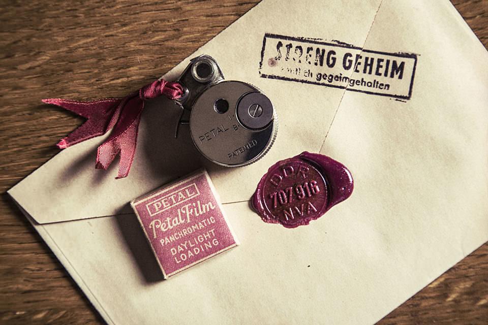 """Briefsache mit Aufdruck """"Streng geheim"""" auf einer Tischplatte mit einer kleinen Minikamera darauf."""
