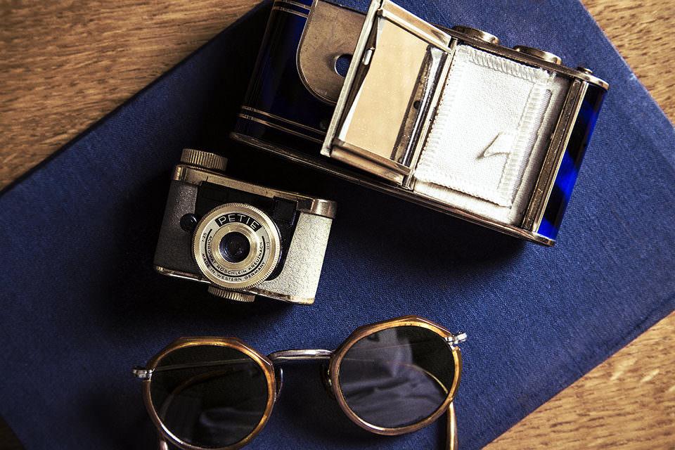 Eine Minikamera, eine Sonnenbrille und eine geöffnete Kamera auf einem Tisch.