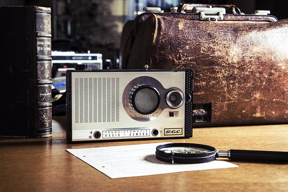 Eine als Radio getarnte Kamera liegt auf einem Holztisch mit Aktentasche dahinter und Lupe davor.