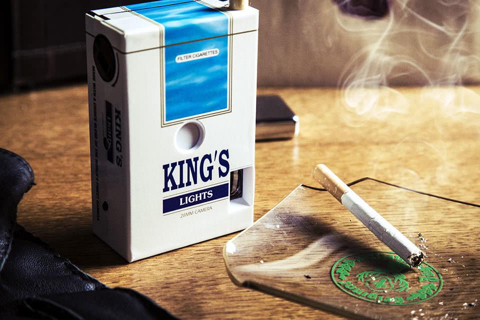 """Eine Zigarettenschachtel aus Plastik mit der Aufschrift """"Kings"""" und einem Lichteinfallloch auf der Vorderseite."""