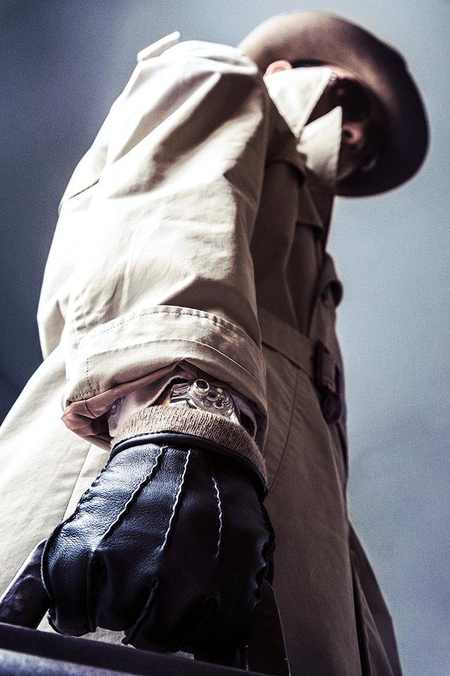 Seitenaufnahme eines Mannes in Mantel und mit Hut, der Lederhandschuhe und ein sonderbares Armband trägt.