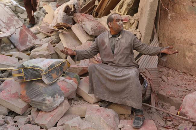 Ein Mann sitzt vor Trümmern