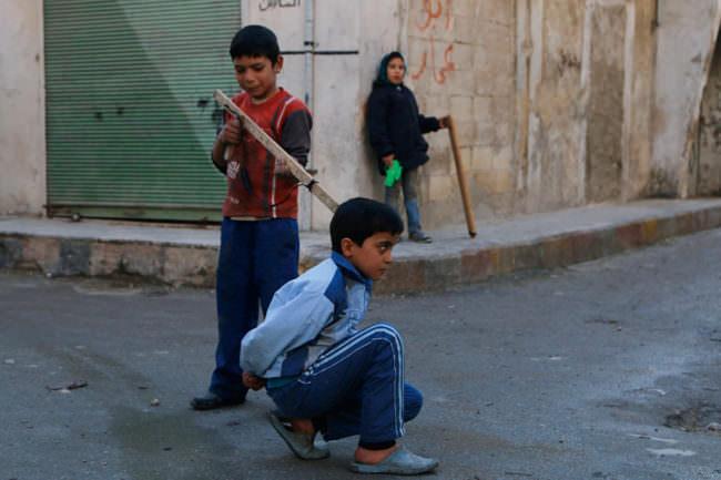 Kinder spielen mit Stöcken Krieg