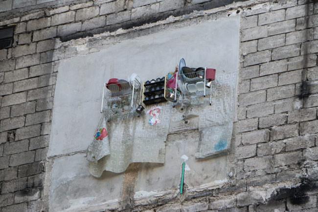 Geschnirr hängt an einem zerstörten Haus