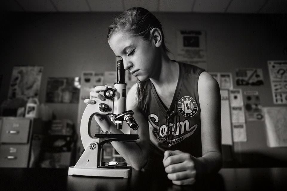 Ein Mädchen sieht durch ein Mikroskop
