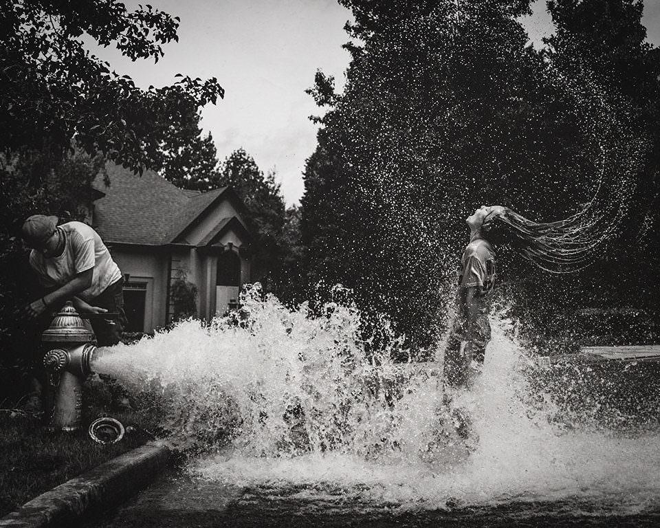 Ein Mädchen badet im Wasser eines Hydranten