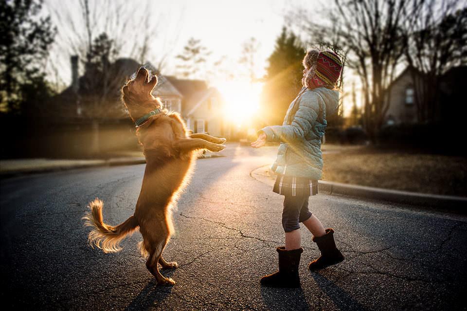 Ein Kind spielt mit einem hund auf der Straße