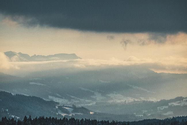 Wolkenverhangener Himmer über einer verschneiten Landschaft