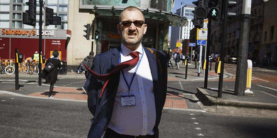 Mann mit Anzug der auf einen zuläuft, seine Jacke ist offen und die rote Krawatte weht im Wind. Er befindet sich in einer städtischen Umgebung.