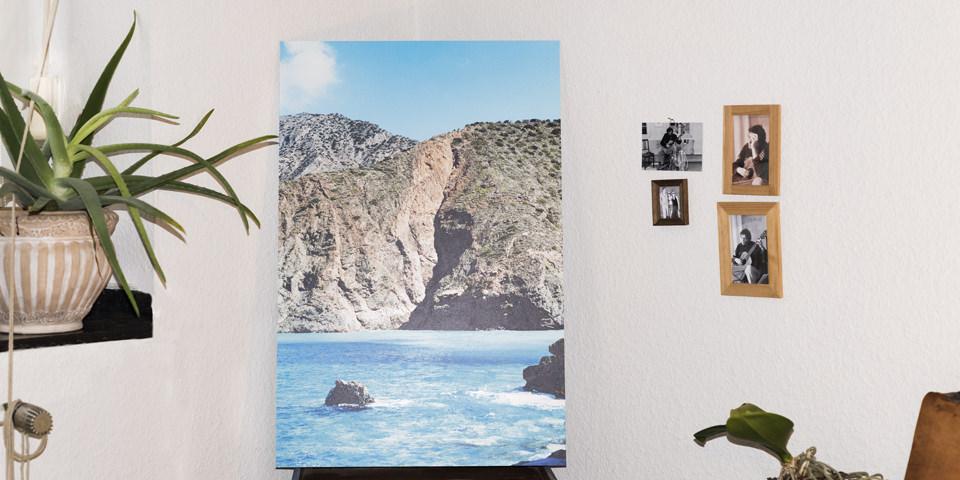 Bild einer Küstenlandschaft mit Türkisen Meer steht in einer Zimmerecke, daneben kleinen gerahmte Fotografien an einer Wand.