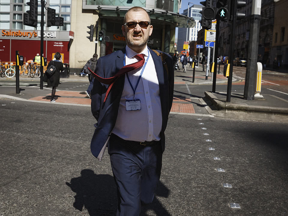 Mann mit Anzug, seine Jacke ist offen und seine rote Krawatte weht im Wind. Er befindet sich in einer städtischen Umgebung.
