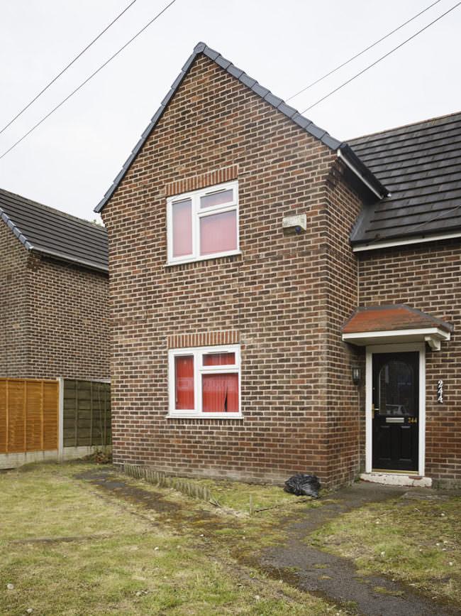 Eine Hausecke eines Backsteinhauses mit zwei Fenstern mit roten Vorhängen.