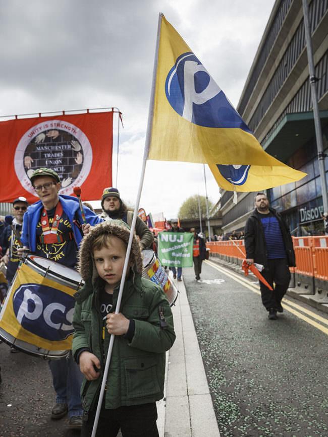 Ein kleiner Junge hat eine gelbblaue Fahne in der Hand auf einem Umzug mit weiteren Fahnenträgern.